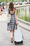 Rear view of a woman pulling a suitcase, Paris, Ile-de-France, France Stock Photo - Premium Royalty-Free, Artist: KL Services, Code: 6108-05873256