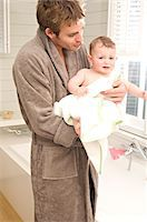 father son bath - Young man in bathrobe with baby in bathroom Stock Photo - Premium Royalty-Freenull, Code: 6108-05873392