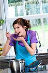 Young smiling woman tasting food Stock Photo - Premium Royalty-Free, Artist: CulturaRM, Code: 6108-05873457