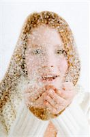 Portrait of a young woman blowing snow from her cupped hands Stock Photo - Premium Royalty-Freenull, Code: 6108-05873573