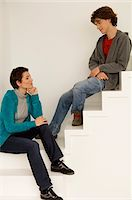 Mid adult woman and her son sitting on a staircase Stock Photo - Premium Royalty-Freenull, Code: 6108-05873612