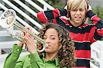 Girl playing a trumpet with her friend covering his ears in the background Stock Photo - Premium Royalty-Freenull, Code: 6108-05873680