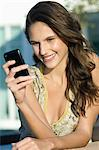 Woman reading text message on a mobile phone Stock Photo - Premium Royalty-Free, Artist: AWL Images, Code: 6108-05873790