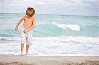Boy playing on the beach Stock Photo - Premium Royalty-Freenull, Code: 6108-05873851