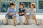 Boy looking through binoculars with his friends sitting beside him Stock Photo - Premium Royalty-Freenull, Code: 6108-05874060