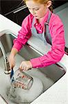 High angle view of a girl washing a measuring jug at a sink Stock Photo - Premium Royalty-Free, Artist: Alison Barnes Martin, Code: 6108-05874099