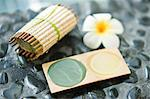 Close-up of a bar of soap with a flower and a tray of mud pack Stock Photo - Premium Royalty-Free, Artist: Blend Images, Code: 6108-05874114