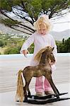 Girl standing near a rocking horse Stock Photo - Premium Royalty-Freenull, Code: 6108-05874147