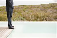 platform - Low section view of a businessman standing on a platform at an infinity pool Stock Photo - Premium Royalty-Freenull, Code: 6108-05874254
