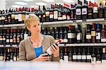 Woman reading a label of a wine bottle Stock Photo - Premium Royalty-Free, Artist: Cultura RM, Code: 6108-05874429