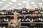 Woman reading a label of a wine bottle Stock Photo - Premium Royalty-Free, Artist: Ikon Images, Code: 6108-05874430