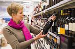 Woman reading a label of a wine bottle Stock Photo - Premium Royalty-Free, Artist: Ikon Images, Code: 6108-05874432