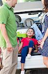 Cute little girl lying in car trunk while parents looking at her Stock Photo - Premium Royalty-Free, Artist: CulturaRM, Code: 6108-05874933