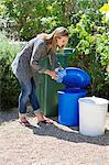 Woman throwing water bottles in garbage bin Stock Photo - Premium Royalty-Free, Artist: Blend Images, Code: 6108-05875009