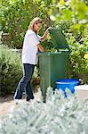 Woman looking into recycling bin Stock Photo - Premium Royalty-Free, Artist: Blend Images, Code: 6108-05875018