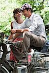 Couple riding bicycles and smiling, Paris, Ile-de-France, France Stock Photo - Premium Royalty-Free, Artist: ableimages, Code: 6108-05875141
