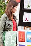 Woman looking at postcards of Eiffel Tower at a market stall, Paris, Ile-de-France, France Stock Photo - Premium Royalty-Free, Artist: Cultura RM, Code: 6108-05875155
