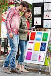 Couple looking at postcards of Eiffel Tower at a market stall, Paris, Ile-de-France, France Stock Photo - Premium Royalty-Free, Artist: CulturaRM, Code: 6108-05875159