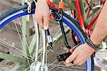 Close-up of a man's hands locking his bicycle, Paris, Ile-de-France, France Stock Photo - Premium Royalty-Free, Artist: ableimages, Code: 6108-05875173