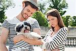 Man carrying a puppy and smiling with a woman looking sad, Paris, Ile-de-France, France Stock Photo - Premium Royalty-Free, Artist: ableimages, Code: 6108-05875195