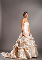 beautiful bride is standing in wedding dress on grey background Stock Photo - Royalty-Freenull, Code: 400-05875644