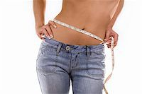 woman measuring her waist wearing blue jeans Stock Photo - Royalty-Freenull, Code: 400-05875928