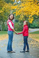 Cute girl with her mother walking in the autumn park. Rain, yellow leaves, tree. Stock Photo - Royalty-Freenull, Code: 400-05876195