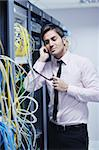 young business man computer science engeneer talking by cellphone at network datacenter server room asking  for help and fast solutions and services Stock Photo - Royalty-Free, Artist: dotshock                      , Code: 400-05878620