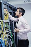 young handsome business man  engeneer in datacenter server room Stock Photo - Royalty-Free, Artist: dotshock                      , Code: 400-05878621