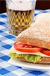 Close-up of an italian panino (sandwich) with freshly baked ciabatta bread, lettuce, cheese and tomato. In the background a glass of beer. Selective focus. Stock Photo - Royalty-Free, Artist: citylights                    , Code: 400-05880641