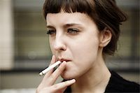 real young woman smokes on the street, selective focus Stock Photo - Royalty-Freenull, Code: 400-05880837