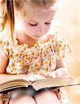 sweet happy little girl reading a book Stock Photo - Royalty-Free, Artist: tan4ikk                       , Code: 400-05881064