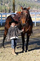 Young boy wearing a cowboy hat with his horse Stock Photo - Royalty-Freenull, Code: 400-05890831