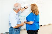 Adult education student working math equations on the board, with her teacher's help. Stock Photo - Royalty-Freenull, Code: 400-05890980