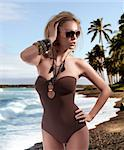 glamour shot of a sexy blonde posing in a brown swimsuit and wearing fashion sunglasses