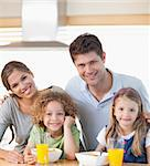 Smiling family having breakfast in their kitchen Stock Photo - Royalty-Free, Artist: 4774344sean                   , Code: 400-05895137