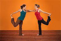 feet gymnast - Two Caucasian women perform yogasana over orange background Stock Photo - Royalty-Freenull, Code: 400-05898844