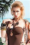 blond sexy beautiful young woman wearing a flower scarf over her body with brown swimsuit with jewellery, she looks in to the lens, has her right hand near the right shoulder and her left hand is on her hip