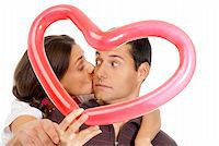 Young couple kissing through baloon heart surprise isolated on white background Stock Photo - Royalty-Freenull, Code: 400-05902204