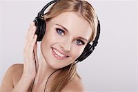 Isolated smiling young girl listening to music Stock Photo - Royalty-Freenull, Code: 400-05907822