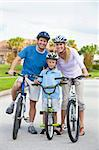 A young family of man and woman parents and one boy child, cycling together. Stock Photo - Royalty-Free, Artist: darrenbaker                   , Code: 400-05907938