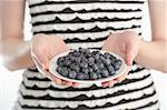 Studio shot of a young woman holding a plate with blueberries Stock Photo - Royalty-Free, Artist: larshallstrom                 , Code: 400-05914358