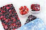 Plastic containers of frozen mixed berries in snow - red currant, cranberry, raspberry, blackberry, bilberry, blueberry, black currant, strawberry Stock Photo - Royalty-Free, Artist: brozova                       , Code: 400-05917121