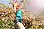 Teenage Girl Bouncing on Trampoline in front of Blooming Tree Stock Photo - Premium Rights-Managed, Artist: ableimages, Code: 822-05948401