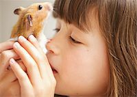 Girl Holding Hamster in front of Face Stock Photo - Premium Rights-Managednull, Code: 822-05948579