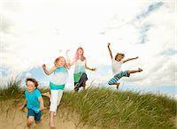 Children playing on grassy sand dune Stock Photo - Premium Royalty-Freenull, Code: 649-05949434