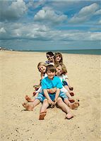 Children sitting together on beach Stock Photo - Premium Royalty-Freenull, Code: 649-05949439