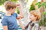 Boy feeling brothers biceps outdoors Stock Photo - Premium Royalty-Freenull, Code: 649-05949581