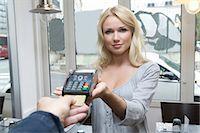 Hostess offering credit card machine Stock Photo - Premium Royalty-Freenull, Code: 649-05949606