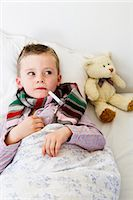 Boy with thermometer in mouth in bed Stock Photo - Premium Royalty-Freenull, Code: 649-05949801